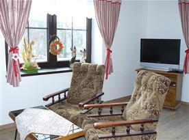 obývací pokoj se sedačkou a TV