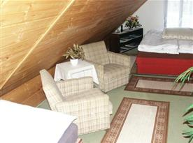 Podkrovní pokoj s lůžky, skříní, křesly a stolkem