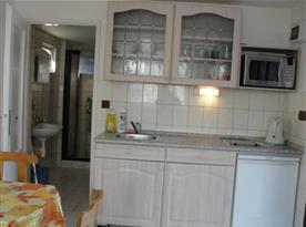 Kuchyňský kout s vařičem, lednicí, stolem a židlemi