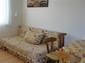Obytná místnost s rozkládací pohovkou a lampičkou
