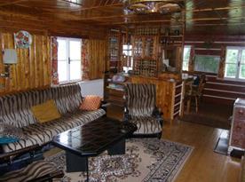Společenská místnost s pohovkou, křesly, stolkem, televizí a skříňkou