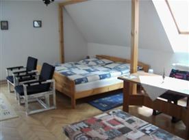 Podkrovní pokoj s manželskou postelí a posezením