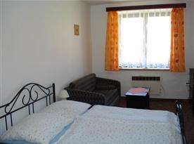 Pokoj s manželským lůžkem, televizí a pohovkou
