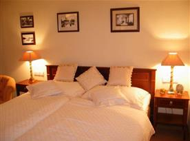 Pokoj manželskou postelí, nočními stolky a lampičkami