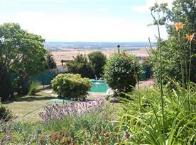Výhled ze srubu na zahradu s bazéneme a krajinu Moravského Toskánska
