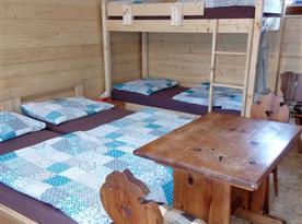 dřevěný interiér chaty včetně povlečených lůžek