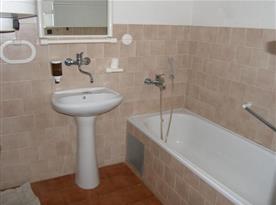 Koupelna s vanou a umyvadlem v apartmánu