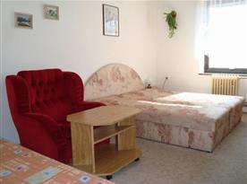 Ložnice s lůžky a posezením v apartmánu