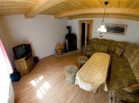 Obývací pokoj se sedací soupravou, krbem a televizí