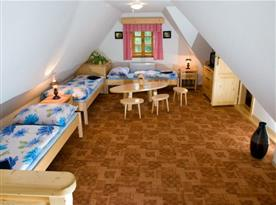 Obytná místnost s lůžky, nočními stolky a televizí