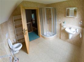Koupelna v patře se sprchovým koutem, toaletou a umývadlem