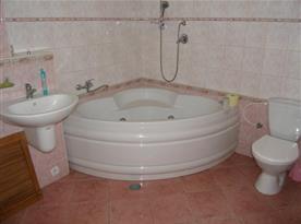 Koupelna v přízemí s rohovou vanou, umývadlem a toaletou