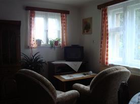 Obývací pokoj s jídelním stolem a křeslem a televizí