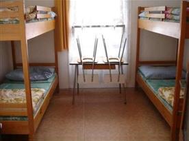 Interiér chatky s palandami, stolkem a židlemi