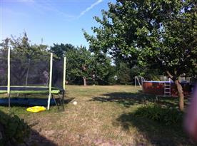 Pohled na zahradu s bazénem a trampolínou