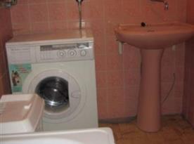 Koupelna v suterénu s vanou, umývadlem a pračkou