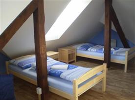 Pokoj s lůžky, nočním stolkem a koupelnou
