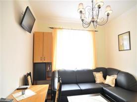 Apartmán se sedací soupravou, stolkem, skříní a televizí