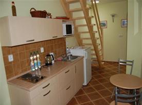 Kuchyně s plotýnkovým vařičem, lednicí, varnou konvicí, stolkem a židlemi