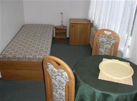 Pokoj s lůžky, nočním stolkem, skříňkou, stolem a židlemi