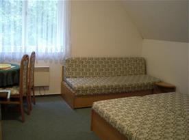 Pokoj s lůžky, pohovkou, stolem a židlemi