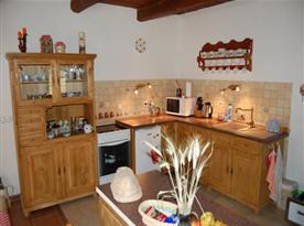 Kuchyňka se sporákem, ledničkou, mikrovlnou troubou a varnou konvicí