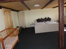 Pokoj s manželskou postelí, nočním stolkem a televizí