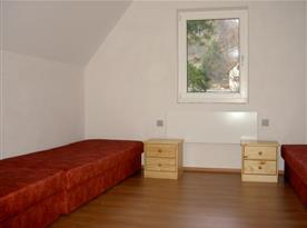 Pokoj s lůžky, nočními stolky a lampičkami