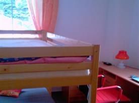 Pokoj s patrovou postelí, psacím stolem, židlemi a skříní