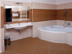 Koupelna s rohovou vanou v apartmánu