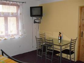Pokoj s lůžky, stolem, židlemi a televizí