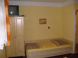 Pokoj s lůžkem, skříní a televizí