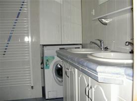 Koupelna se sprchovým koutem, umývadlem, zrcadlem a pračkou