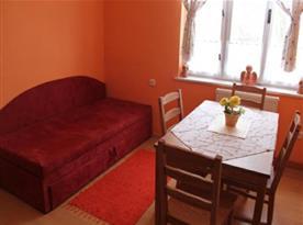 Obývací pokoj s gaučem a jídelním posezením