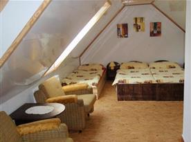 Ložnice s lůžky, nočními stolky, lampičkami a posezením