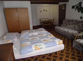 Pokoj s lůžky, sedačkou a jídelním posezením