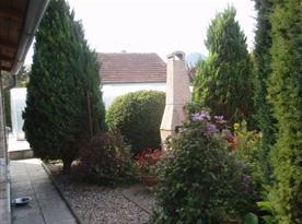 Pohled na zahradu se zahradním krbem u posezení