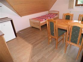 Kuchyně s lůžkem a jídelním stolem v podkroví