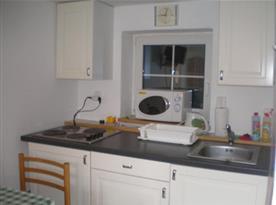 Kuchyňka v suterénu s linkou, lednicí, elektrickým vařičem, mikrovlnou troubou a rychlovarnou konvií
