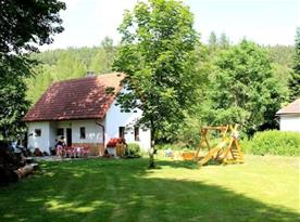 Pohled na chatu v zahradě s posezením