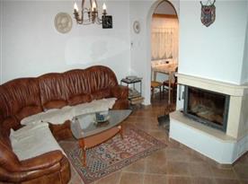 Obývací pokoj s koženou sedačkou, krbem a televizí