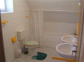 Koupelna s vanou, toaletou a dvěma umyvadly