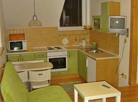 Podkrovní kuchyňka B s jídelním koutem a televizí