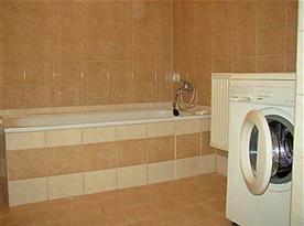 Koupelna v suterénu s vanou a automatickou pračkou