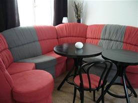Obývací pokoj s velkou rohovou sedačkou a televizí