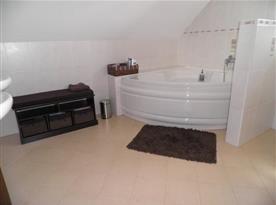 Sociální zařízení v patře s rohovou vanou, toaletou a umyvadlem