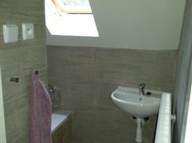 Koupelna v patře s vanou a umyvadlem