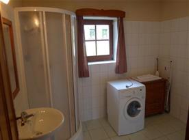 Koupelna se srpchou, umyvadlem a automatickou pračkou