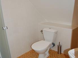 Sociální zařízení v podkroví s toaletou a sprchovým koutem