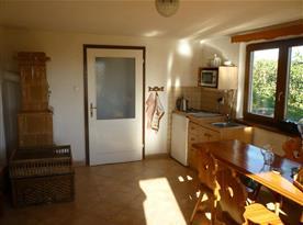 Společenská místnost se stylovým selským nábytkem, kachlovými kamny a kuchyňkou